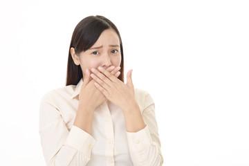 口を塞ぐ女性