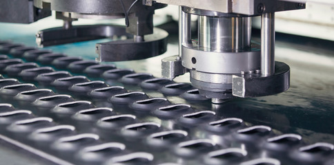 Rotation CNC Punching & Nibbling Machine in action. Metal perforating industrial machine.