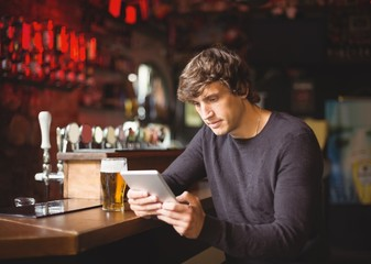Man using digital tablet at bar counter