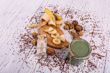 healthy green smoothie with walnut and fruits lie on the table