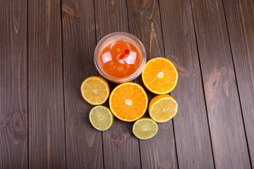orange detox coctail with half orange,lemon and lime lies on tab