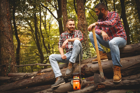 Two friends Lumberjack worker sitting in the forest .Resting after hard work.
