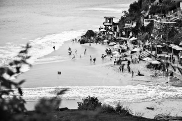 INDONESIA, BALI - JANUARY 19, 2012: Coast of the tropical island with people on the beach, top view. Black-white photo on January 19, 2012 in Indonesia, Bali.