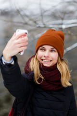 Smiling blonde girl doing selfie