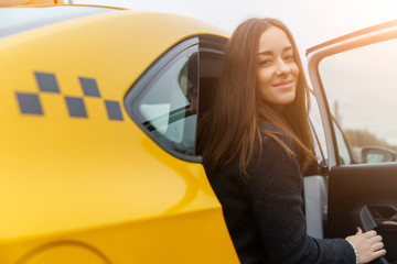 Happy beautiful woman sits in yellow taxi