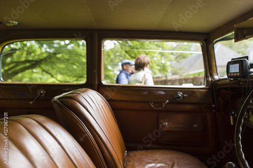 brown leather interior of a classic vintage car on display in a park with people in the. Black Bedroom Furniture Sets. Home Design Ideas