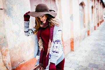 sensual stylish lady walking on the street  in hat.