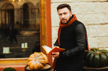 handsome and young man in a black coat reading a book outdoors