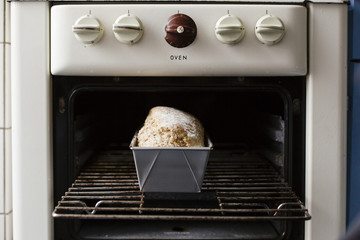 Fresh baked loaf of bread in a vintage oven.