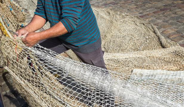 Commercial fisherman mending nets in the port, France