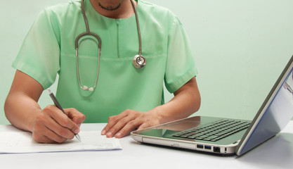 Doctor working with computer notebook at desk