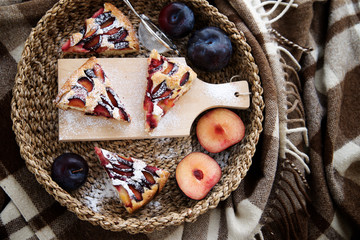 The cozy day. Plum cake on wicker tray and plaid