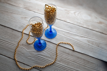 new years eve party table with champagne. Champagne glasses. Celebration theme. New dekor- beads, garland instead of champagne. Festive glasses with champagne.