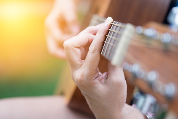 Close up on young woman playing guitar with morning light