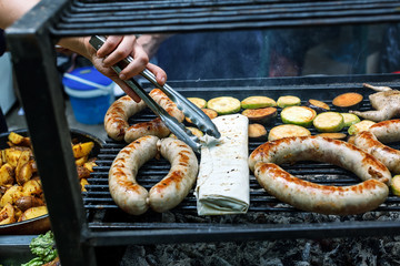 Grilling sausages and quail on the market showcase