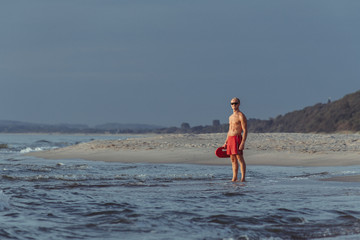 lifeguard on the beach with glasses, with a life buoy, wet sand and sea at sunset