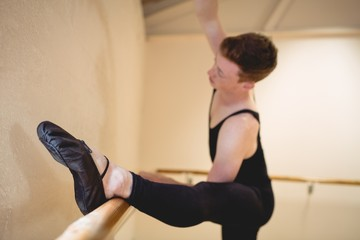 Ballerino stretching on a barre while practising ballet dance