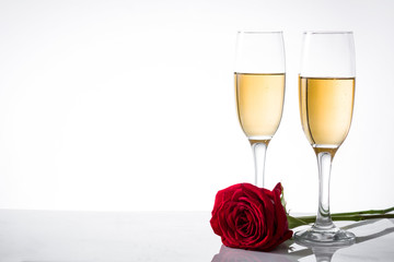 Champagne cup and red rose on white background