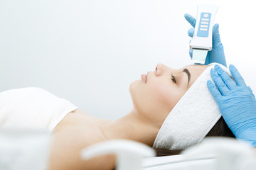 Doctor doing procedure of ultrasonic cleaning of face