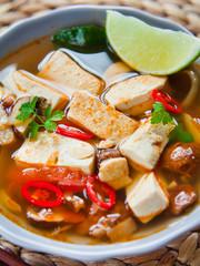 vegetarian asiani broth pho soup with fried tofu, shiitake mushrooms and lime