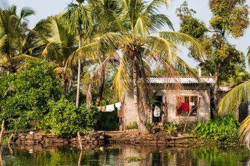 Small house on edge of back water canal in Kerala India with clothes drying on clothes line