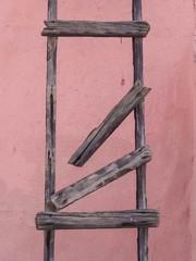 alte zerbrochene Holzleiter vor einem blassrosa Hintergrund