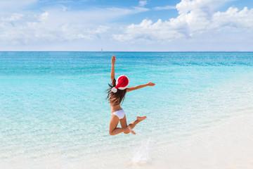Wall Mural - Happy Santa hat girl jumping of joy and fun on Christmas holiday travel in tropical beach destination. Winter vacation getaway woman.