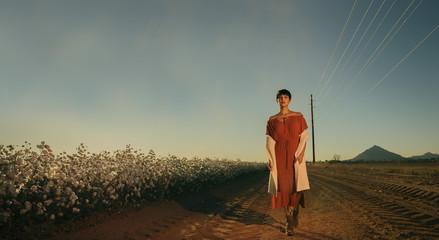 Beautiful young woman walking alone alongside cotton field on devil gravel road in Arizona,USA,
