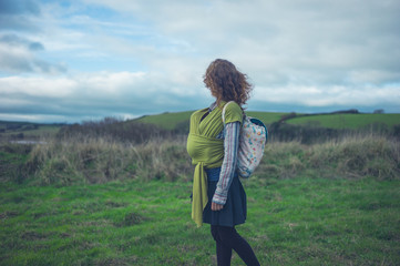 Mother walking in countryside with baby in sling