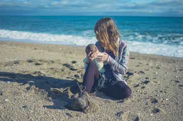 Mother sitting on beach with baby