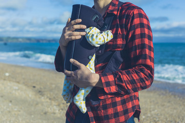 Father with baby in carrier on beach