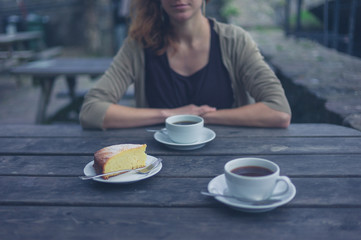 Woman having coffee and cake outside