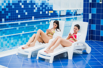 Young girls friends messaging with friend on her smartphone. Relaxation spa and technology social networks concept.