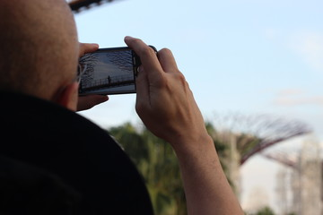 Tourist take a Pic of Garden by the Bay, Singapore, with His Mobile Phone