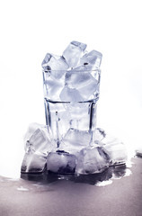 A glass with ice stands on a white background with a pile of ice cubes at the bottom. Chaotic scattered icicles . Winter background. New Year pattern.