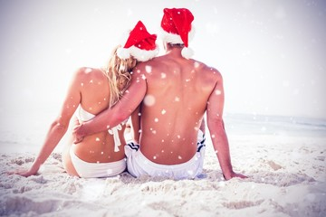 Composite image of rear view of couple with santa hat sitting to