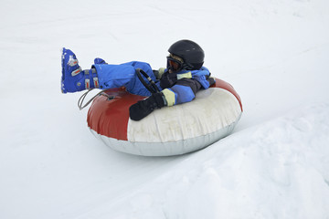 A child boy (wearing ski helmet) having fun sledding on a tube in the snow.