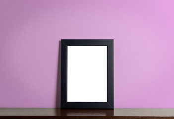 Blank photo frane on wooden shelf with pink background.