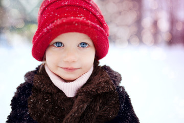 Little girl in the red hat on the snow street