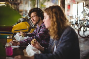 Couple sitting at table and eating sandwich