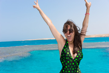 Woman in black-green swimsuit raising her hands up and laughing