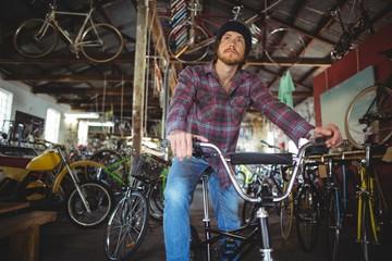 Thoughtful mechanic sitting on bicycle