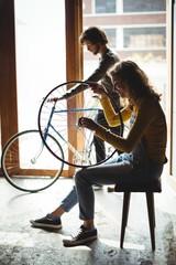 Mechanics examining a bicycle wheel