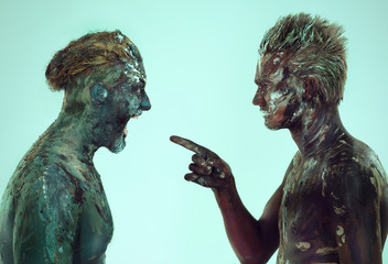 two men expressive portrait screaming at each other in body art painted,in the studio on a green background
