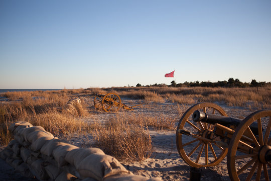 Civil war battle flag of The Citadel Military College flown over a cannon near Fort Sumter, Charleston, South Carolina