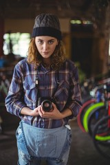 Woman adjusting vintage camera in bicycle shop
