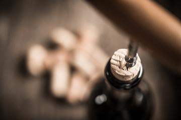 Opening wine bottle with corkscrew in restaurant