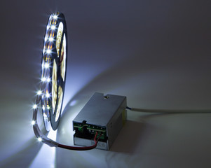 Spool of luminous LED strip light connected to Power Supply.