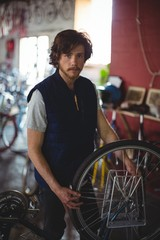Portrait of mechanic examining bicycle
