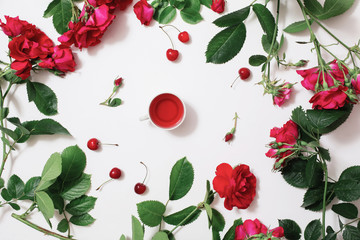 Red karkade tea in a white mug, ripe cherries, frame of roses with green leaves on a white background. Juice, juice from the berries. A refreshing drink. Flat lay, art, copyspace, top view.